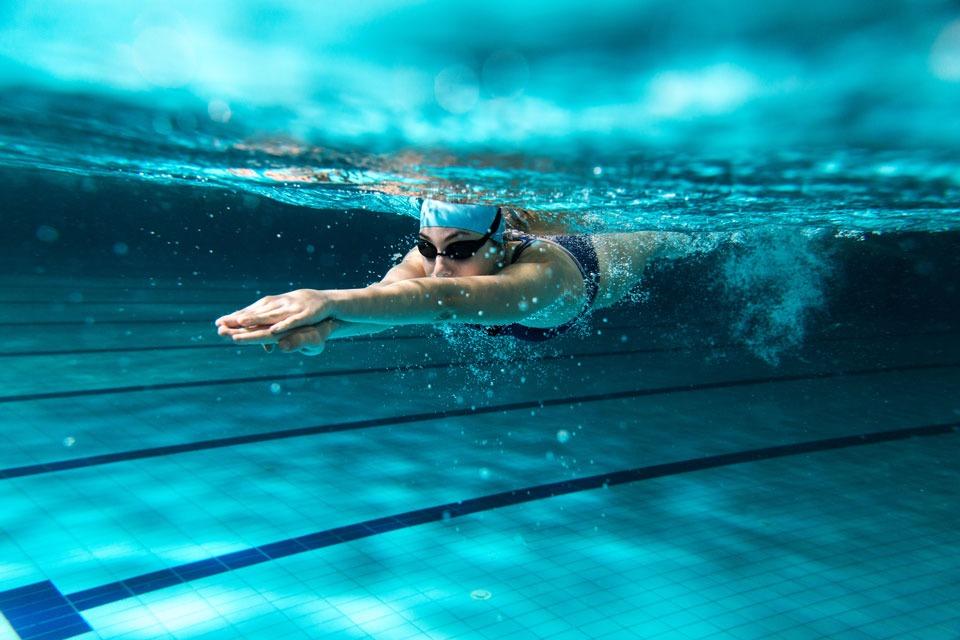 femme natation avec des protections auditives