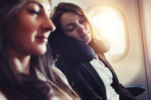 femme dormant dans un avion avec des protections auditives